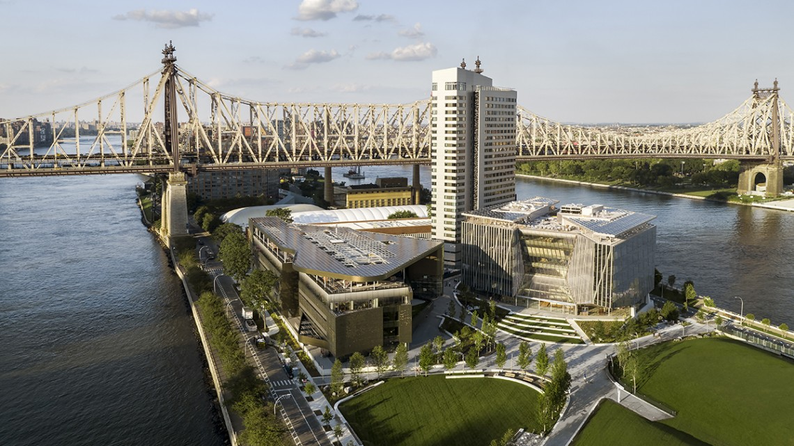 An aerial view of the Cornell Tech campus, showing the 59th Street Bridge over Roosevelt Island and the Great Lawn, in the foreground.