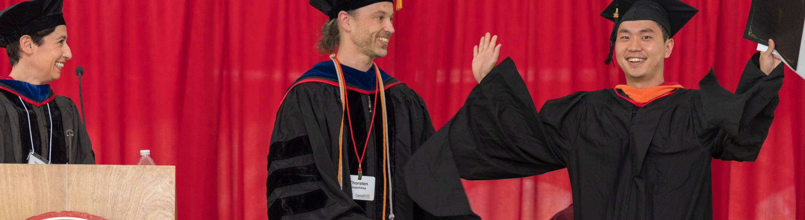 An MPS graduate receives his diploma during Info Sci's 2018 Commencement ceremonies.